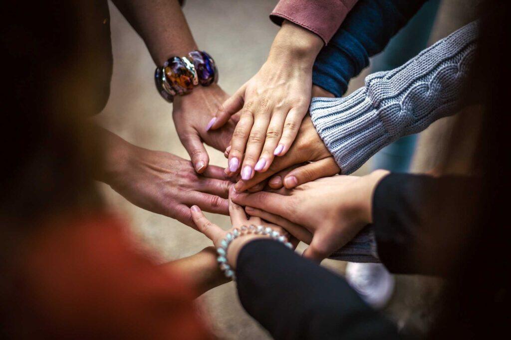 Varias manos uniéndose en el centro haciendo un equipo