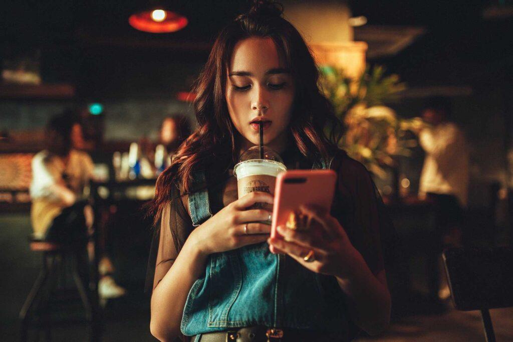 Chica con teléfono en manos leyendo artículos